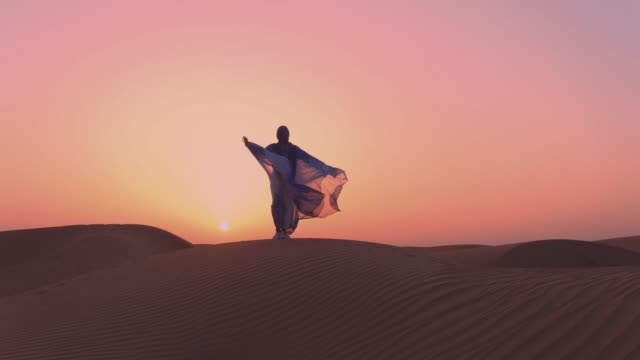 Women wearing beautiful blue and white Arab clothes rising her hands at the desert Women wearing beautiful blue and white Arab clothes rising her hands at the desert east stock videos & royalty-free footage