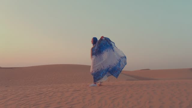Women wearing beautiful blue and white Arab clothes rising her hands at the desert Women wearing beautiful blue and white Arab clothes rising her hands at the desert turkey middle east stock videos & royalty-free footage