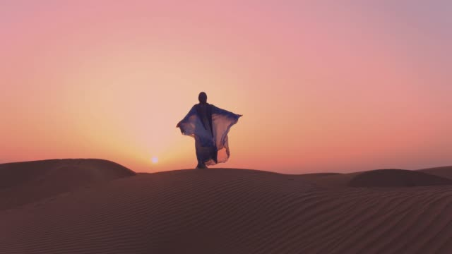 Women wearing beautiful blue and white Arab clothes rising her hands at the desert