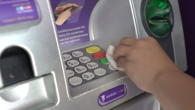 Women wearing plastic glove before use the ATM machine Women wearing plastic glove before use the ATM machine. Avoid covid-19 or Corona virus attack banks and atms stock videos & royalty-free footage