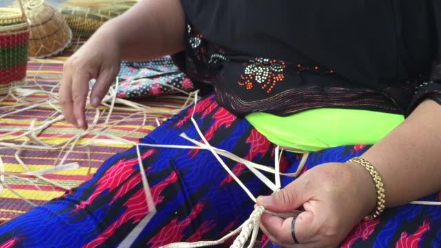 Women weaving making wicker basket video