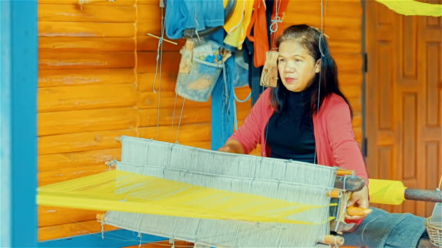 Women weaving the silk threads into fabric on a loom at home in countryside of Thailand video