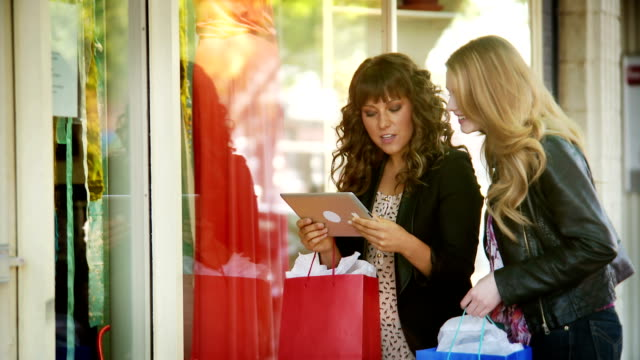 Women window shopping with tablet Two women window shopping and looking for the best deals by accessing the internet with their tablet.  They are relaxing and having fun together on their day off in the meantime they build strong friendships and bonds that will last forever.  The laugh and smile because they are so excited at what they have discovered in the store. wisdom stock videos & royalty-free footage