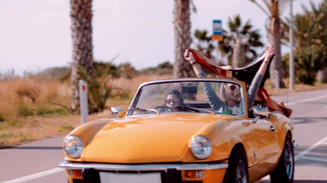 frauen mit amerikanischen flagge fahrendes cabriolets auto am meer - spring break stock-videos und b-roll-filmmaterial