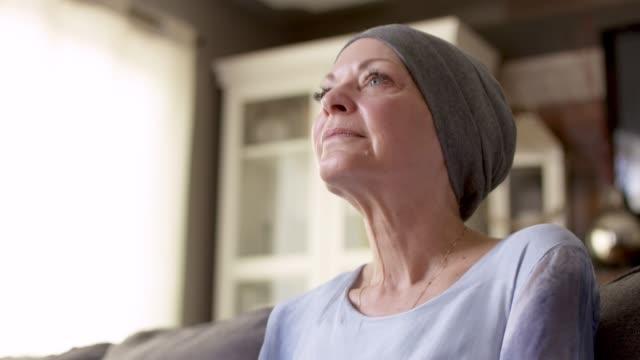 vídeos de stock, filmes e b-roll de as mulheres com cancro sentam-se em seu sofá em casa - cancer de mama