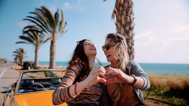 stockvideo's en b-roll-footage met vrouwen met converteerbare auto hart vorm met de handen maken - tienermeisjes