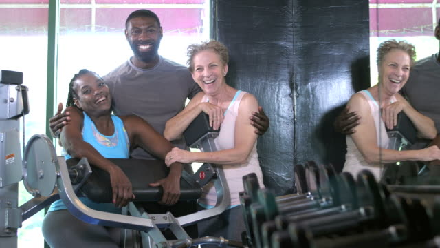 women with fitness instructor at the gym - tre persone video stock e b–roll