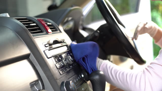 a women with hand glove wiping down on surfaces of car interior for cleaning covid-19 virus - igiene video stock e b–roll