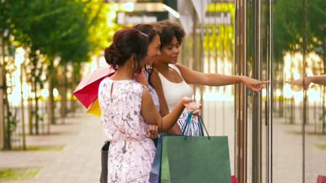 women with shopping bags looking at shop window - fare spese video stock e b–roll