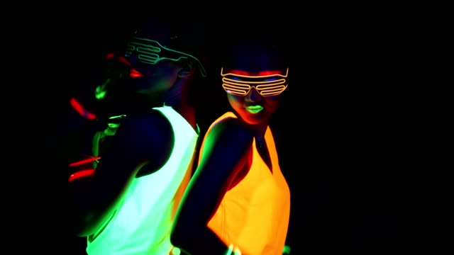 Women with UV face paint, glowing bracelets, glowing glasses, clothing dancing back against each other in front of camera, Half body shot. Caucasian and asian woman. Women. video