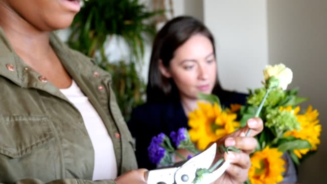 women working in florist shop creating flower arrangements for customer - stelo video stock e b–roll