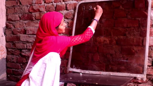 vidéos et rushes de femmes d'écriture sur tableau noir - extérieurs d écoles