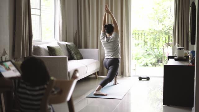 vídeos de stock e filmes b-roll de women yoga exercise at home - treino em casa