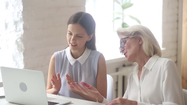 Women young employee helping to elderly colleague with online program Young and elderly businesswomen sitting at desk in workplace use laptop talk discuss online task, younger employee helps to mature colleague with corporate program, teamwork support mentoring concept prop stock videos & royalty-free footage