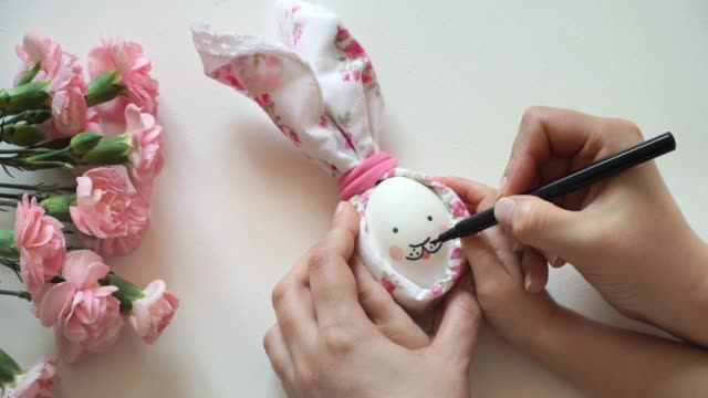 Women's and children's hands hold chicken egg decorated for Easter bunny in hands, paint rabbit's face with marker.