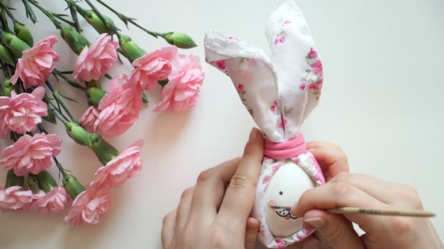Women's and children's hands hold chicken egg decorated for Easter bunny, paint egg with brush pink cheeks.