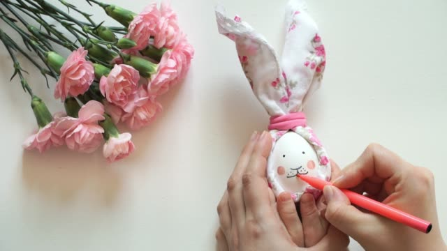 Women's and children's hands hold chicken egg decorated for Easter bunny, paint rabbit's face with pink marker.