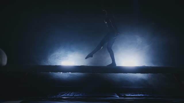 konstnärlig gymnastik för kvinnor. i slow motion i röken, utför flickan komplexa delar av det olympiska programmet på en balans balk - på tå bildbanksvideor och videomaterial från bakom kulisserna