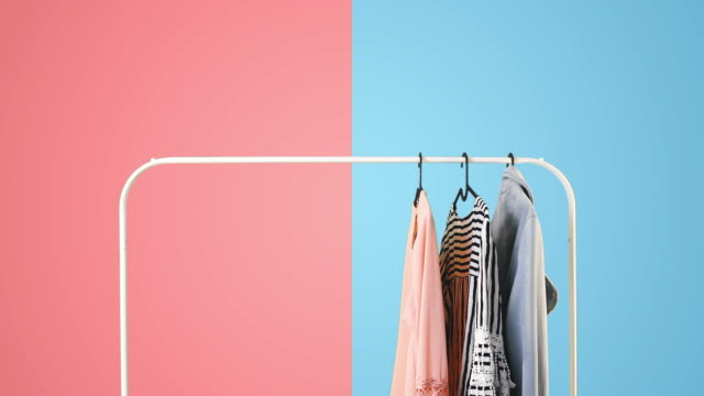 Women's clothing on a white clothes hanger on pink and blue pastel colors background. Women's clothing on a white clothes hanger on pink and blue pastel colors background. dress stock videos & royalty-free footage