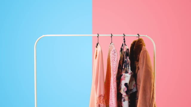 Women's clothing on a white clothes hanger on pink and blue pastel colors background. Women's clothing on a white clothes hanger on pink and blue pastel colors background. coathanger stock videos & royalty-free footage