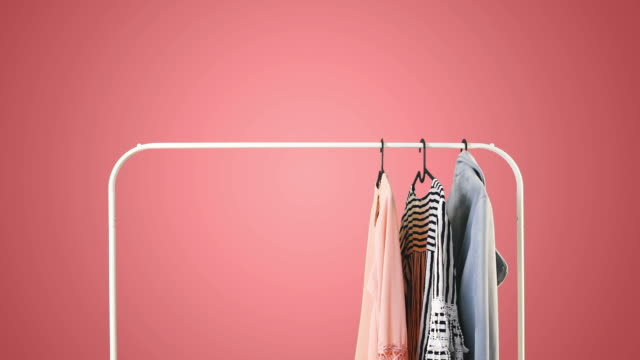 Women's clothing on a white clothes hanger on pink pastel background. Women's clothing on a white clothes hanger on pink pastel background. coathanger stock videos & royalty-free footage