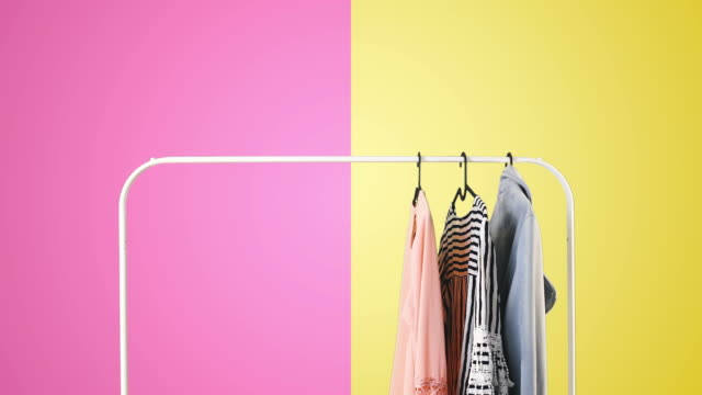 Women's clothing on a white clothes hanger on violet and yellow pastel colors background. Women's clothing on a white clothes hanger on violet and yellow pastel colors background. coathanger stock videos & royalty-free footage