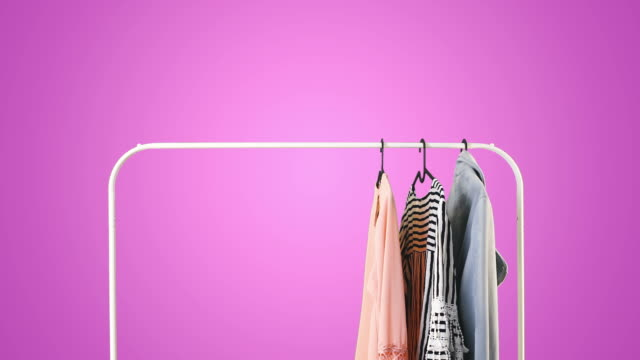 Women's clothing on a white clothes hanger on violet pastel background.