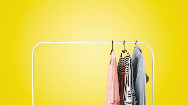 women's clothing on a white clothes hanger on yellow pastel background. - вешалка стоковые видео и кадры b-roll