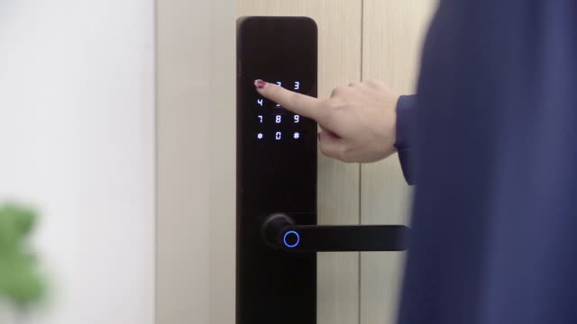 Women's finger pressing the security code on digital lock of the door.