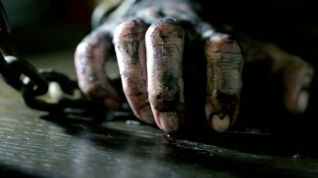 Women's fingers with dirty fingernails and burned skin. female hand shackled. video