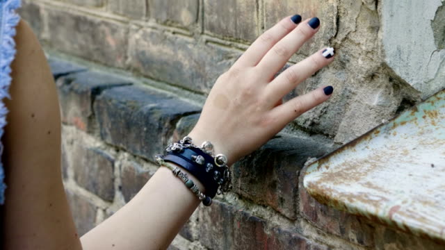 Women's hand with a black leather wristband moving along the brick wall. 4K