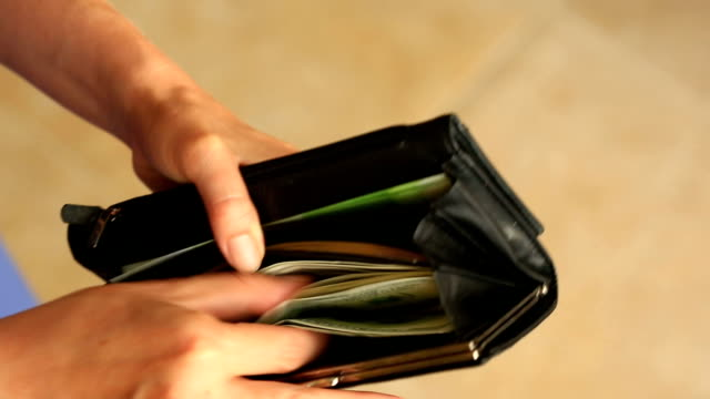 Women's hands hold a money clip with dollars video