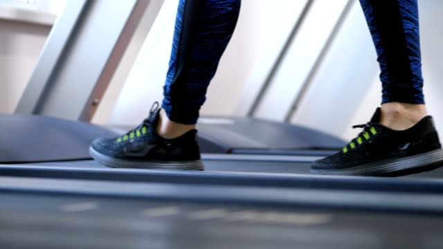 women's legs are slowly walking on the treadmill. 4k slow mo - runner rehab gym video stock e b–roll