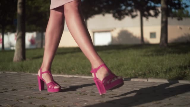 Women's legs are walking in the center of the city. Businesswoman wearing pink shoes with heels. Women's legs are walking in the center of the city. Businesswoman wearing pink shoes with heels. Stylish woman walking in the city center. stepping stock videos & royalty-free footage