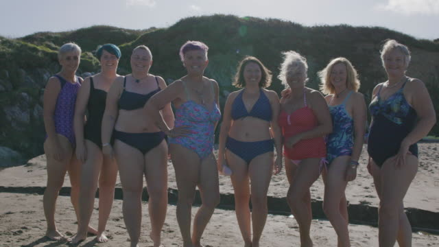 A women's swimming club having a laugh together as they line up for a group photograph on an empty beach.