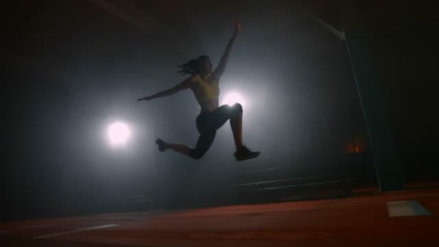 vidéos et rushes de athlétisme féminin au ralenti, effectuant un saut en longueur avec un départ en course. sauter dans le sable lors des compétitions - athlétisme