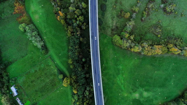wonderful aerial view with a drone over a highway road in france. only grass fields and trees around the roads. cars and trucks driving on the roads under the sun. - francja filmów i materiałów b-roll