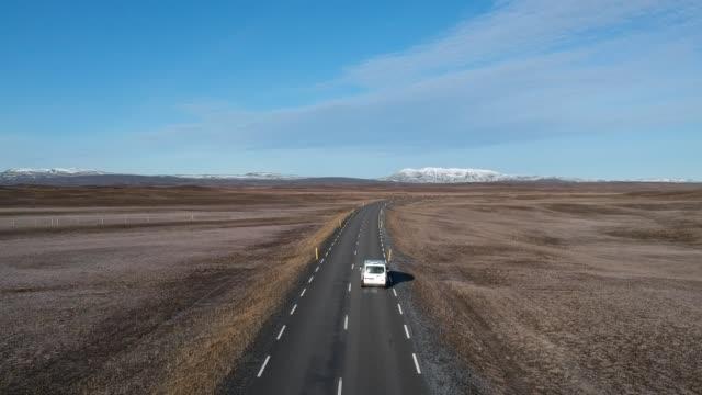 stockvideo's en b-roll-footage met een prachtig droneschot van twee reizigers en een camper met meer en bergenachtergrond. - caravan