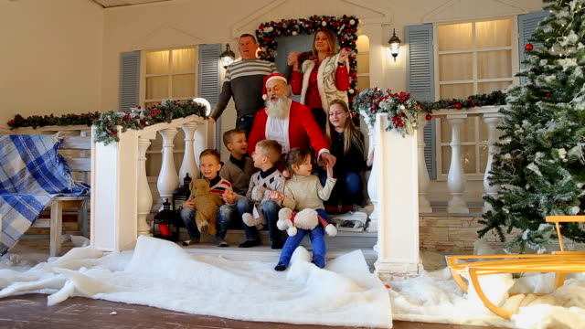 Wonderful family, together with Santa, have fun and in good mood to meet Christmas on porch of decorated house video