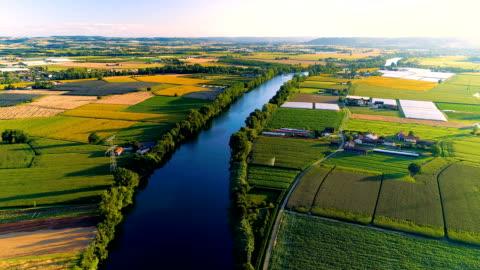 vídeos de stock e filmes b-roll de wonderful shot of a river and fields with a drone - cena rural