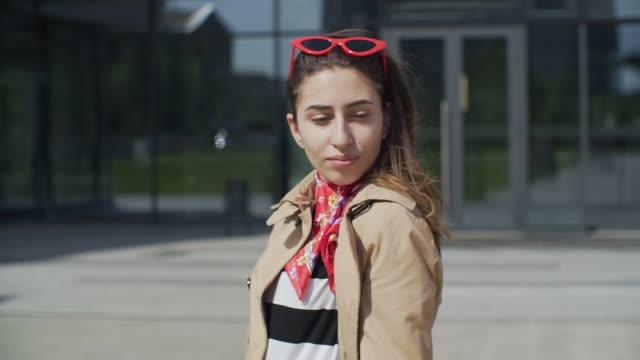 wonderful smiling woman in red sunglasses with a lovely look and natural make up looking at camera and the wind moving her hair - kiss стоковые видео и кадры b-roll