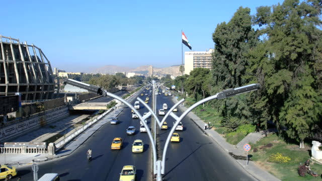 Wonderful view over circulation in Damascus. A lot of cars on the road in Syria, with the national flag in the background. View over the circulation in Damas, a lot of cars and trucks on the road. A living city even after the war. Buildings and trees in the background. War years in Syria. damascus stock videos & royalty-free footage