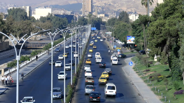 Wonderful view over circulation in Damascus, Syria. A busy highway in the capital. View over the circulation in Damas, a lot of cars and trucks on the road. A living city even after the war. Buildings and trees in the background. War years in Syria. damascus stock videos & royalty-free footage