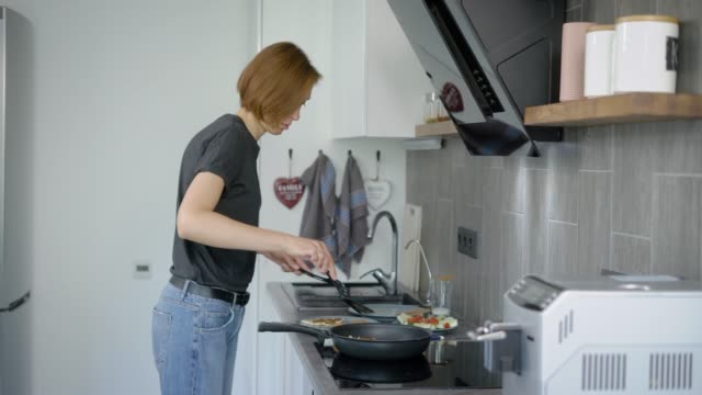 Wonderful woman with short red hair cooking delicious breakfast at home video