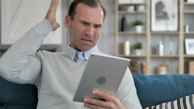 Wondering Middle Aged Man in Shock by Loss while Using Tablet