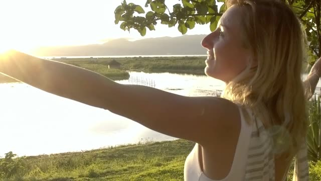 Wonderlust- Woman embracing freedom in nature caucasian female arms outstretched by the lakeshore