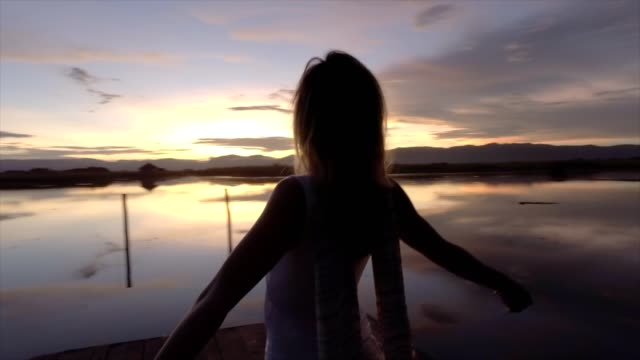 Wonderlust- Woman embracing freedom in nature Silhouette of caucasian female arms outstretched on wooden lake pier,