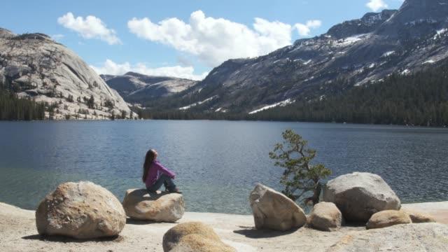 vídeos de stock, filmes e b-roll de wonderlust mulher sentada na pedra, apreciando a tranquilidade do lago isolado na primavera - penedo