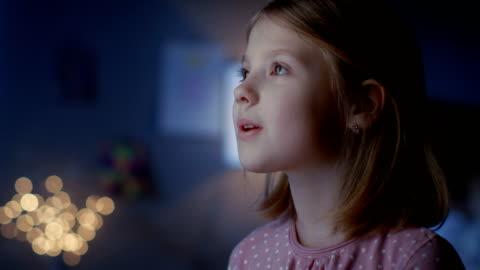 vidéos et rushes de wondrous fille heureusement regarde par la fenêtre. - petites filles