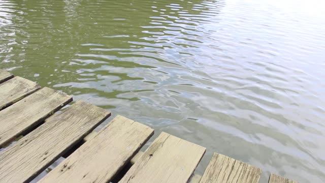 träbro på floden som har promenad sätt med vatten vågor långsamt. - flod vatten brygga bildbanksvideor och videomaterial från bakom kulisserna